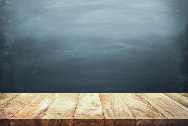 Foco seletivo do tampo da mesa de madeira em desfocar o fundo do quadro-negro escuro. para criar a exibição do produto ou projetar o layout visual chave.