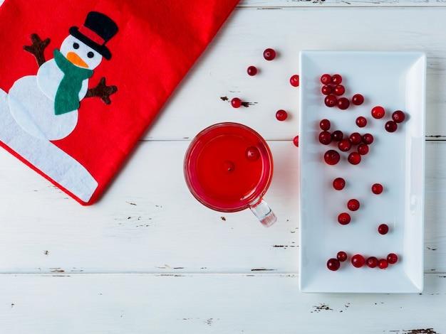 Foco seletivo em cranberries em uma bebida fresca em um copo de vidro. bagas em um prato branco. bolsa vermelha com a foto de um boneco de neve. decoração de ano novo em um fundo branco de madeira. copie o espaço. postura plana.