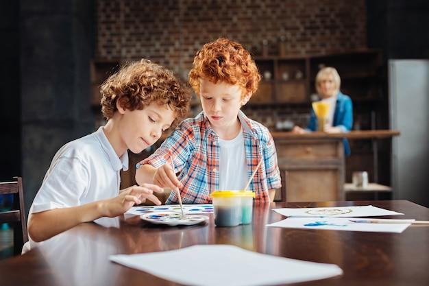 Foco seletivo em crianças criativas que se encontram em uma mesa e pintam com aquarelas enquanto passam o dia em casa com uma avó de pé ao fundo.
