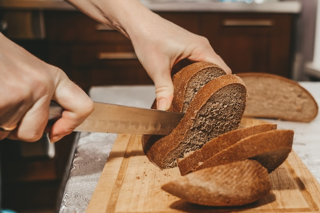Foco seletivo em fatias de pão de centeio cortadas de um pão com uma faca. pão em uma tábua de madeira de cozinha.