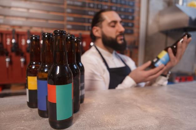 Foco seletivo em garrafas de cerveja no balcão, barman examinando a garrafa de cerveja