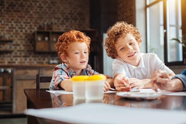 Foco seletivo em irmãos de cabelos cacheados inteligentes sentados à mesa e escolhendo aquarelas em uma paleta enquanto trabalham em sua nova obra-prima.