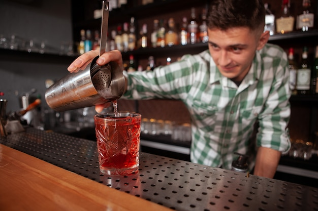 Foco seletivo em um barman profissional de bebida derramando para o copo. coquetéis, conceito de ocupação