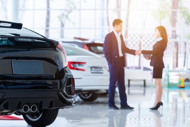 Foco seletivo em um carro novo e desfoque o vendedor profissional da concessionária e seu cliente, apertando as mãos. conceito profissionalismo contrato contrato leasing aluguel de carros de varejo.