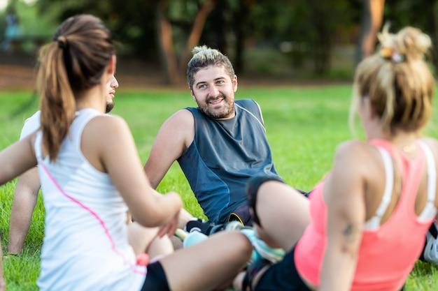 Foco seletivo em um homem entre um grupo de amigos com saquê em linha em um parque