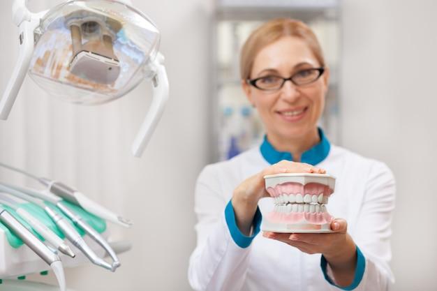 Foco seletivo em um molde dental nas mãos de um dentista maduro
