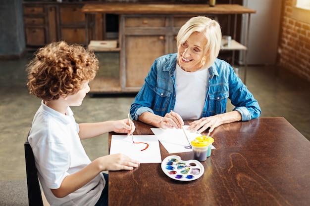 Foco seletivo em uma bela senhora idosa olhando para seu neto de cabelos cacheados enquanto lhe perguntava sobre algo durante uma sessão de pintura em família