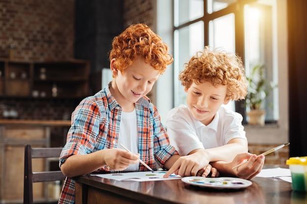 Foco seletivo em uma criança ruiva vestindo uma camisa xadrez, ouvindo seu irmão mais velho dando conselhos e apontando para um pedaço de papel enquanto os dois pintavam em casa.