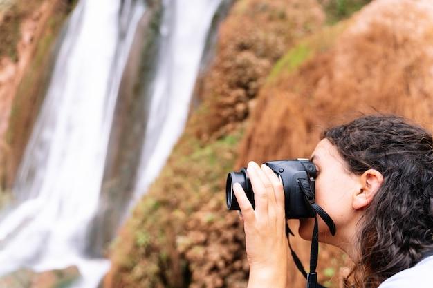 Foco seletivo em uma mulher tirando uma foto das cachoeiras de ouzoud com uma câmera digital. cachoeiras de ouzoud em marrocos