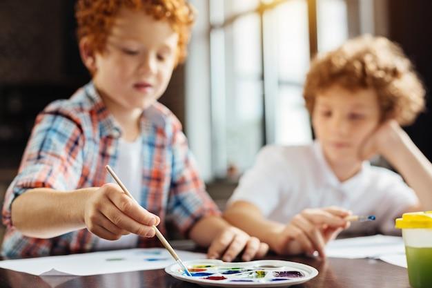 Foco seletivo em uma paleta com diferentes tons de aquarelas e a mão de um pequeno artista segurando um pincel e escolhendo um tom de tinta enquanto pinta com o irmão.