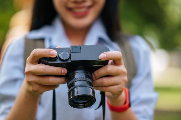 Foco seletivo, fechar a mão de uma jovem fotógrafa segurando uma câmera digital enquanto viaja, copie o espaço