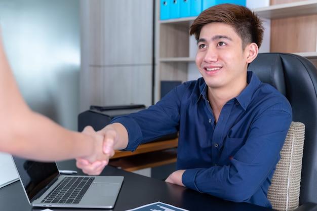 Foco seletivo jovem aperto de mão com alguém no escritório