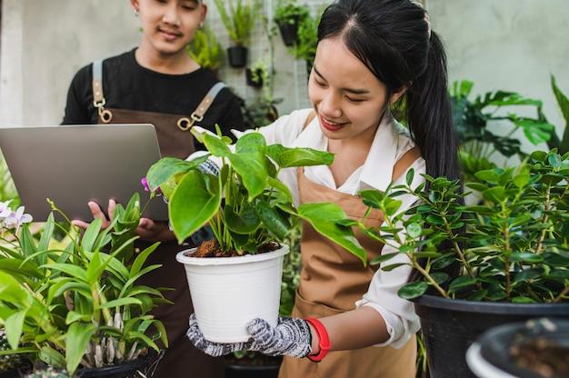 Foco seletivo, jovem casal de jardineiros asiáticos vestindo avental usa equipamento de jardim e um laptop para cuidar