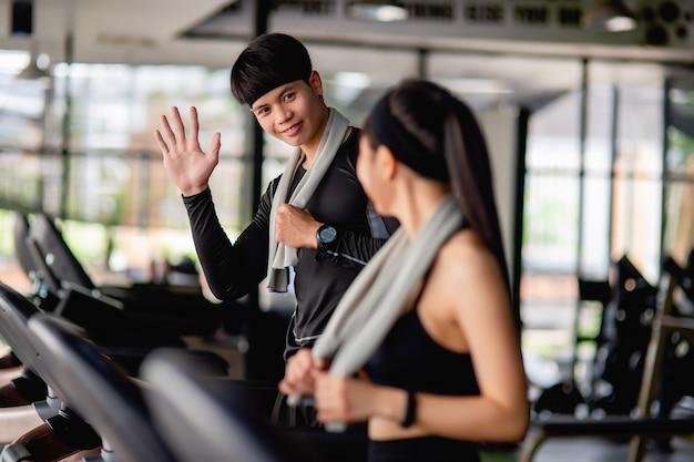 Foco seletivo, jovem esportista sorri e levanta a mão para cumprimentar uma linda mulher e um retrato desfocado senhora sexy em roupas esportivas na esteira, eles estão se exercitando em uma academia moderna, copie o espaço