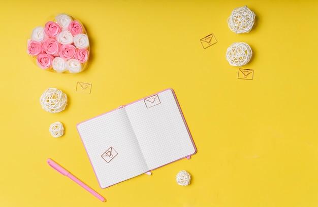 Foco seletivo. layout do dia dos namorados. bloco de notas rosa com copyspace. sobre um fundo de papel amarelo com artigos de papelaria. a vista do topo