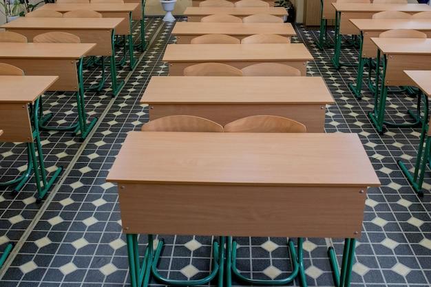 Foco seletivo macio e desfoque. cadeiras de leitura de fileira de madeira velha na sala de aula na escola pobre. sala de estudo sem aluno. conceito de educação
