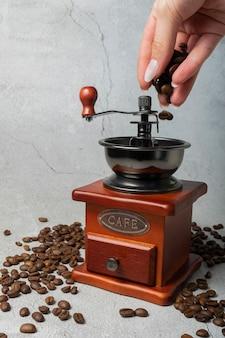 Foco seletivo. moinho de café retro manual. madeira escura sobre um fundo cinza claro. com café escrito em letras de metal