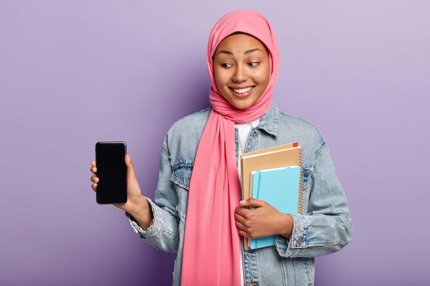 Foco seletivo. mulher alegre e charmosa com pele escura usando lenço de seda rosa na cabeça