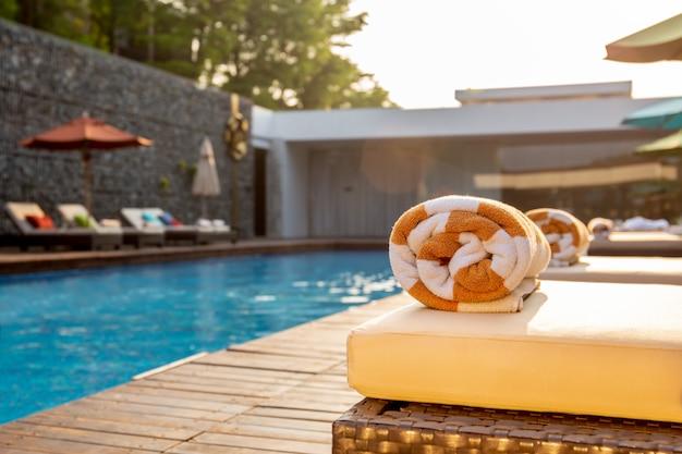 Foco seletivo na associação de toalha na cama da praia em torno da piscina no hotel.