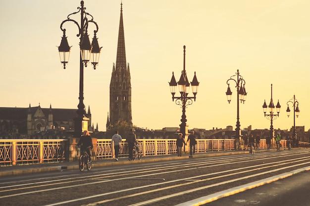 Foco seletivo na catedral de saint michel, pessoas andando de bicicleta na ponte pont de pierre em bordeaux durante o pôr do sol