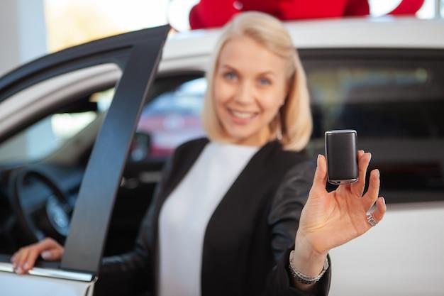 Foco seletivo na chave do carro na mão de uma bela motorista do sexo feminino