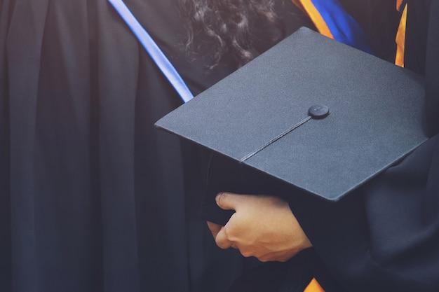 Foco seletivo na graduação da frente da graduação feminina na fila da cerimônia de formatura