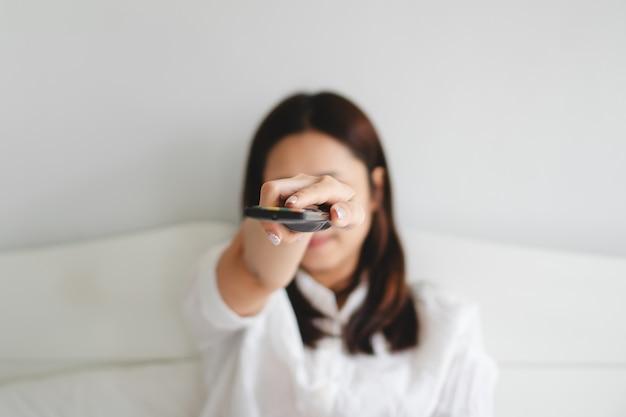 Foco seletivo na jovem mulher que olha a tevê e que mantém o controlo a distância disponivel.