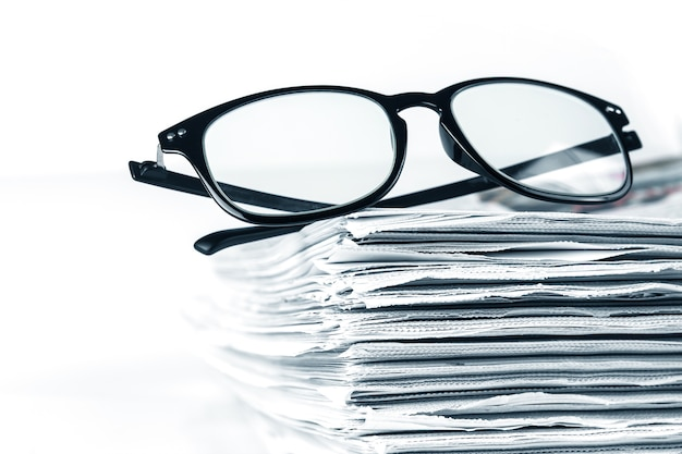 Foco seletivo na leitura de óculos com empilhamento de fundo de jornal