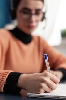 Foco seletivo na mão do aluno, fazendo anotações no caderno para exame universitário, antes da reunião on-line no zoom. mulher jovem com fone de ouvido fazendo a lição de casa enquanto está sentada à mesa da escrivaninha na sala de estar