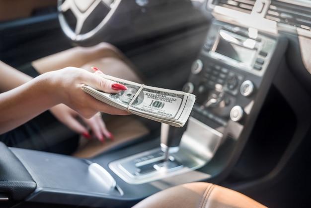 Foco seletivo na mão feminina com um pacote de dólares dentro do carro