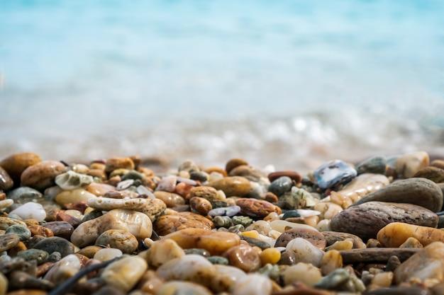 Foco seletivo na textura de rochas com praia de borrão no fundo.