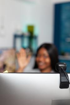 Foco seletivo na webcam do computador enquanto um estudante afro-americano cumprimenta o professor
