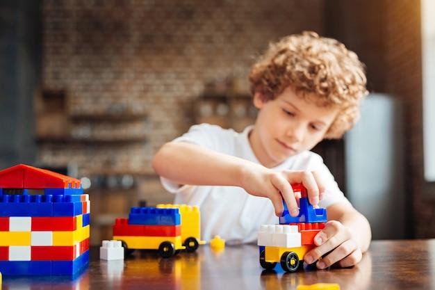 Foco seletivo nas mãos de um menino de cabelo encaracolado inteligente, sentado à mesa e projetando o carro dos sonhos, enquanto brincava com uma construção em casa.