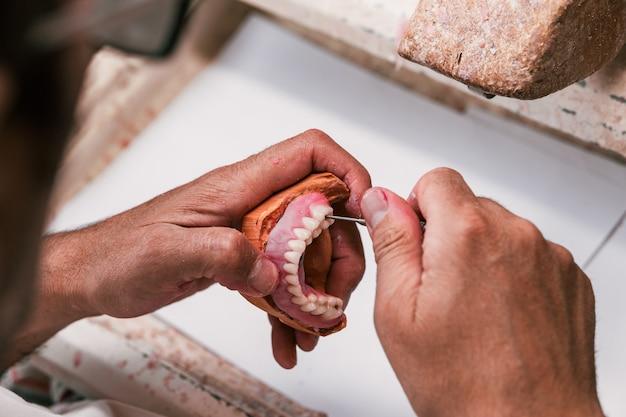 Foco seletivo nas mãos de um técnico de prótese dentária que fixa uma prótese dentária em uma oficina