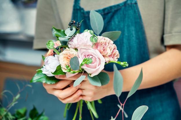 Foco seletivo no buquê de flores nas mãos femininas. mulher de florista fazendo bando na loja. conceito de floricultura, negócios, venda e produtos de floricultura. copie o espaço para o design