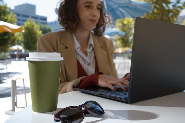 Foco seletivo no café e óculos escuros, no fundo mulher latina trabalhando no laptop, conceito nômade digital.