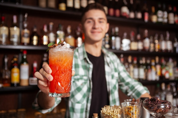 Foco seletivo no copo de cocktail barman alegre segurando para a câmera