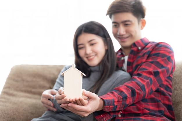 Foco seletivo no jovem casal da mão segurando a mini casa de madeira no sofá no quarto