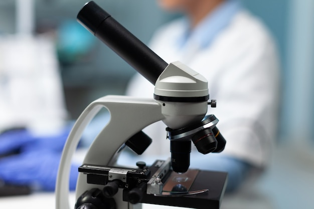 Foco seletivo no microscópio médico em pé na mesa de um hospital de bioquímica