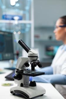 Foco seletivo no microscópio médico em pé na mesa do laboratório de bioquímica do hospital