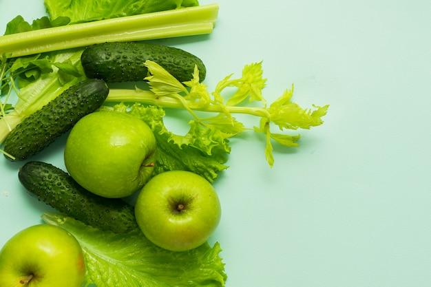 Foco seletivo, nutrição desintoxicante, dieta verde em vegetais e frutas. produtos naturais em um fundo azul