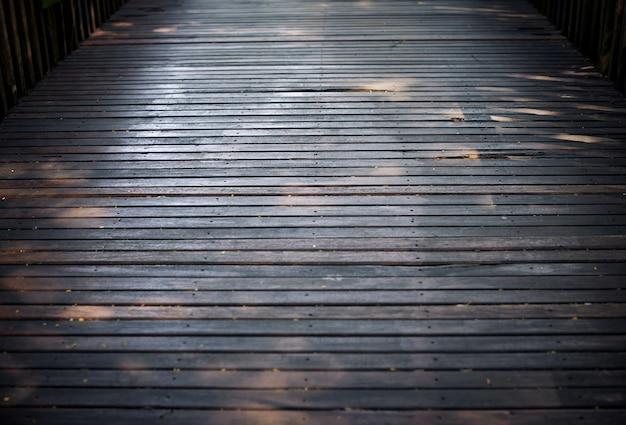 Foco seletivo o assoalho de madeira duro velho da ponte com fundo sujo da textura.