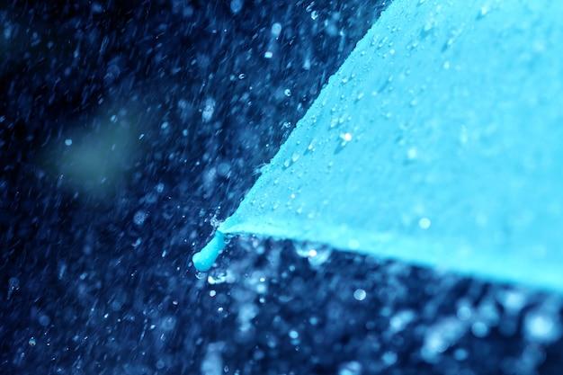 Foco seletivo para fechar uma parte do guarda-chuva que tem gotas de chuva caindo, dof raso