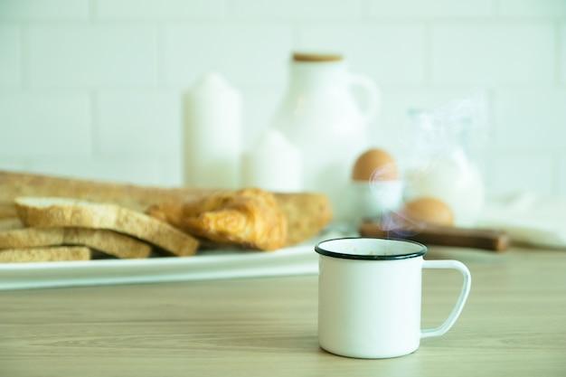 Foco seletivo tom branco do café da manhã com uma xícara de café preto, croissant de pão e leite