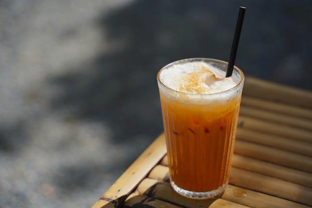 Foco seletivo, um copo de chá com leite de laranja tailandês com leite fresco para fazer chá e uma camada de leite