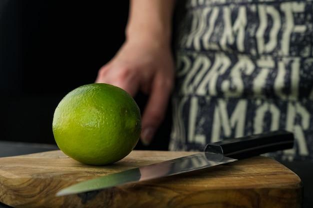 Foco seletivo, uma garota em um avental cinza fatiar limão em uma placa de madeira