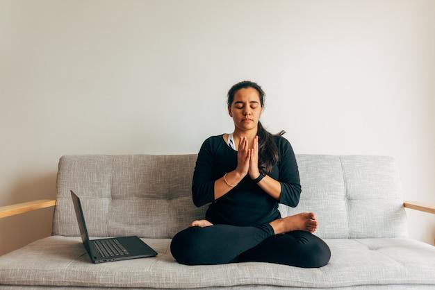 Foco seletivo: uma mulher latina sentada fazendo ioga, assistindo a uma aula online dentro de casa. conceito de ioga em casa. copie o espaço