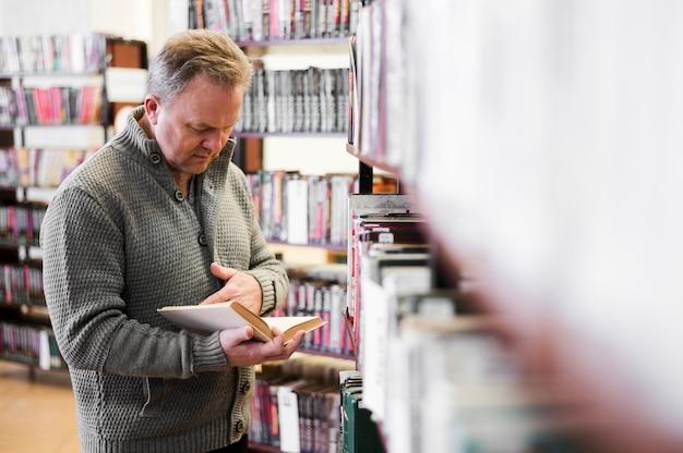 Foco sênior homem olhando para livro