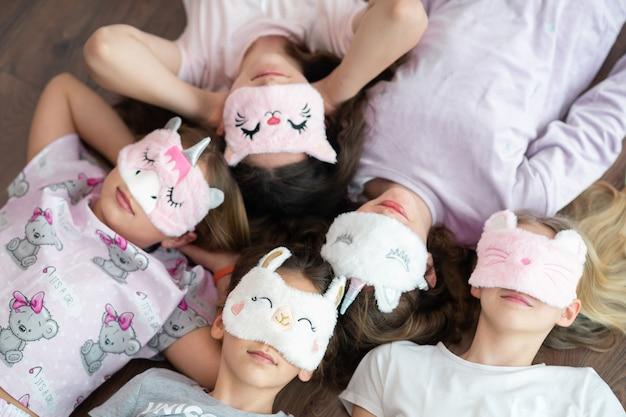 Foco suave. cinco garotas com faixas de dormir de pele em forma de unicórnio deitam-se no chão e riem. festa do pijama.