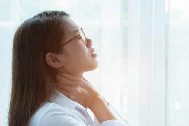 Foco suave da jovem empresária com óculos, sentindo-se exausto e sofrendo de dor no pescoço